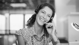 Smiling woman on phone assisting customer