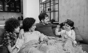 Family sitting under blankets.